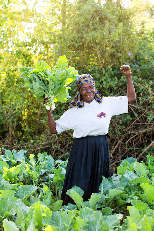 Sarah, a farmer in Kenya, with the crops she's growing with the help of her irrigation pump. like