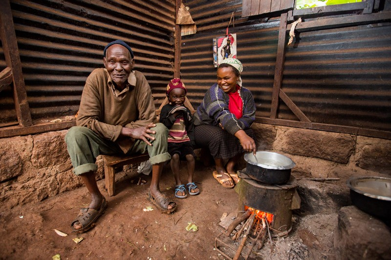 Mary, a mother from Kenya, cooking with her family using her brand new fuel-efficient stove.