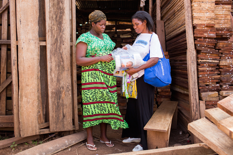 Joy, a health care promoter working in Uganda with one of her repeat customers.